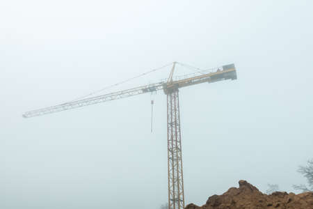 Tall construction crane in fog early morning