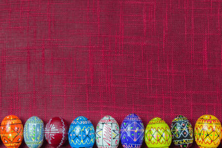 Row of colorful rustic wooden Easter eggs on red color background with copy space