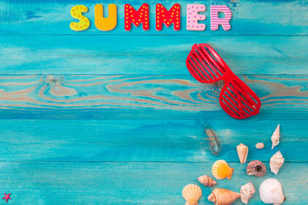 Top view summer holidays background concept with louvered shades and seashells on blue wooden table