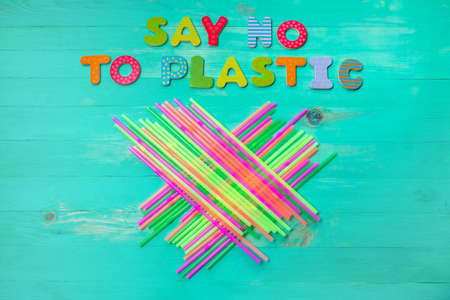 Say no to plastic - colorful wooden letters phrase on green wooden background with plastic straws, top view