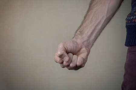 Aggressive man threatens with clenched fist. Violence and aggression concept.