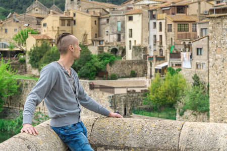 Man looking at traditional European cityscape - ancient houses of Middle Ages in Besalu, Girona, Catalonia, Spain, South Europe Reklamní fotografie