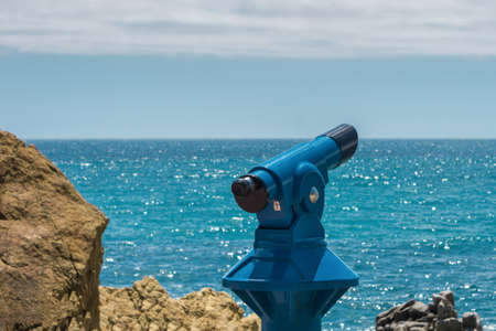 Binoculars telescope for tourists and travelers, sea and sky background. Observation overlooking the Mediterranean sea from beach.
