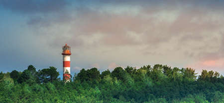 Panoramic view of lighthouse in forest at dusk sky background showing way for ships in sea