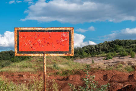 Old rusty information abandoned signboard in countryside landscape