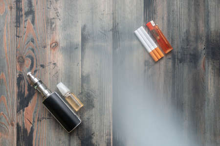 Flat lay of e-cigarette and e-liquid versus tobacco cigarettes with lighter on wooden background, covered smoke 免版税图像