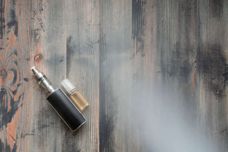 Flat lay of e-cigarette and e-liquid on wooden background, covered smoke Reklamní fotografie