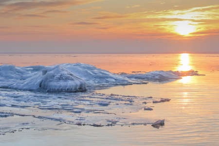 Winter landscape in colorful dramatic sunset with packed ice in the Baltic sea