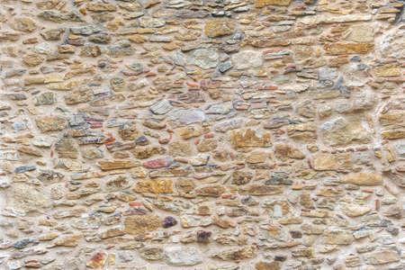 Pietre gialle e muro di mattoni. Sfondo di superficie in mattoni e pietra