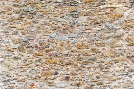 Yellow stones and bricks wall. Brick and stone surface background