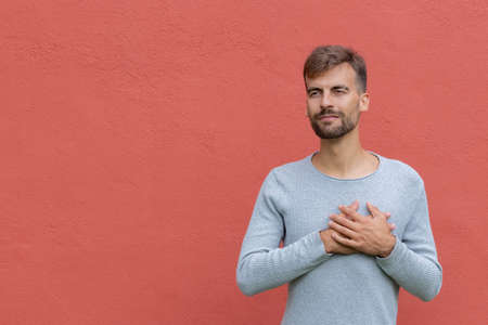 Good-natured handsome guy keeping hands on heart, showing love and sympathy over red wall background with copy space. Body language and love feeling concept Stock fotó