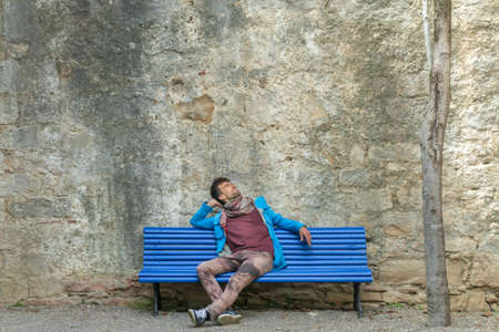 Young romantic handsome man sitting alone on bench in front ancient fortress stone wall and waiting for dating