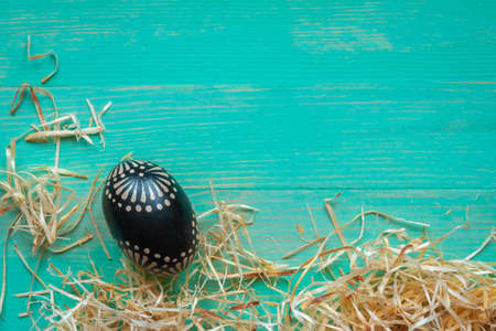 One wooden black painted patterned Easter egg with hay straws around on vintage turquoise color wooden background. Rustic style. Copy space. Top view. Flat lay.