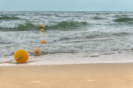 Swimming place on beach and in sea area fenced with rope with floats. Seaview with swimming area fenced with buoys