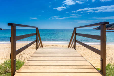 Boardwalk to sandy beach. Wooden walkway over sand to sea. Sunny beach with wooden walk floor. Vacation background. Summer vacation concept. Copy space. 스톡 콘텐츠