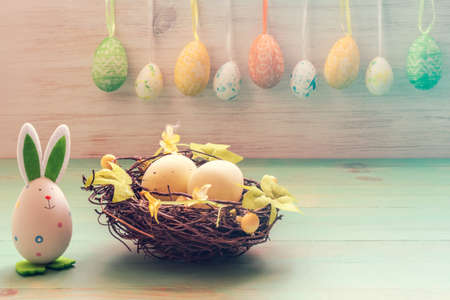 Nest of twigs with eggs, cute bunny toy and row of Easter eggs on vintage wooden background. Easter holiday decoration