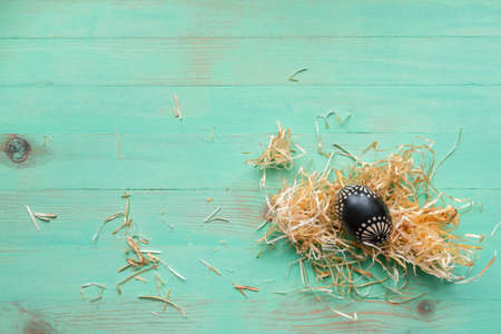 Wooden black painted patterned Easter egg and hay straws around on wood background
