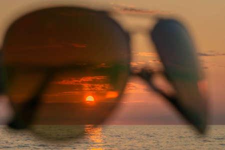 Setting sun, evening sky, and sea through sunglasses in seacoast. Sundown in sea through eyeglasses. Concept of summer holidays with beach scene in sunset through sunglasses