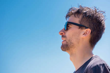 Man portrait with sunglasses looking ahead on sky background