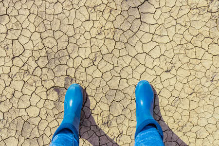 Texture of dry cracked earth surface with human foot in boots from above. Cracked patch of land, no vegetation. Dry land, affected by drought, dramatic impact on environment. Global warming concept. Stock Photo