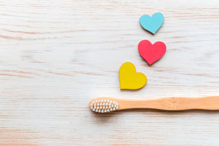 Natural bamboo toothbrush and wood hearts on wooden background. Biodegradable bamboo toothbrush. Natural product. Flat lay, top view, copy space. Zero-waste, eco-friendly, plastic-free concept