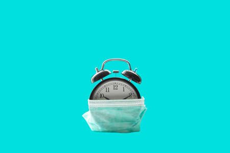 Medical protective mask putting on alarm clock isolated on azure background. Alarm clock with medical mask on isolated background. Prevent coronavirus. Quarantine and time to stay home concept.