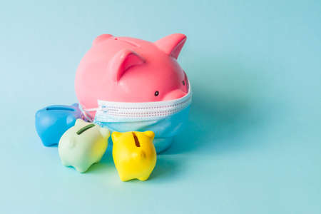 Pink piggy bank, wearing protective facemask and around small piggy banks, isolated on blue background. Piggy bank with medical mask and other around. Money saving concept during coronavirus pandemic.