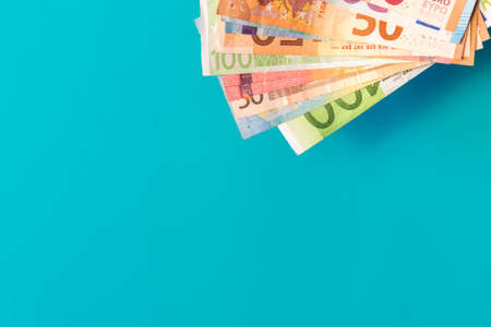 Euro banknotes isolated on blue background with soft shadows. Euro notes in corner on azure background with copy space. Euro cash of different values. Bunch of European money. Stock fotó