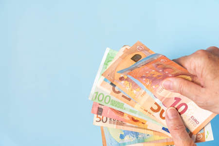 Hands holding European banknotes isolated on blue background. Person hands with euro notes on azure backdrop. Euro cash of different values in hands on background with copy space
