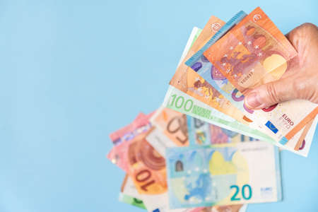Person hand holding euro notes and other blurred banknotes on blue background. Hand with European banknotes isolated on azure backdrop. Euro cash of different values in hand. Copy space.
