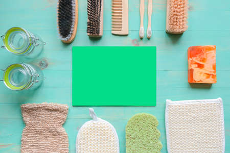 Bamboo toothbrushes, natural sponges, wooden comb, solid soap, natural bristle wood brushes, and reusable glass jars with green copy space. Zero-waste lifestyle and eco-friendly concept. Flat lay
