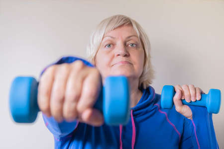 Senior woman doing her exercises with dumbbells