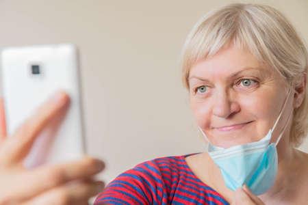 Elderly woman using mobile phone taking selfie
