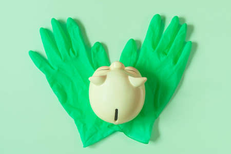Piggy bank on rubber gloves isolated on background