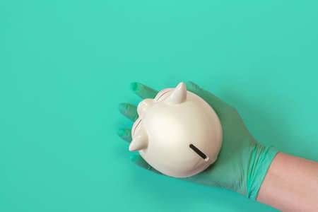 Hand in rubber glove holding piggy bank on isolated background