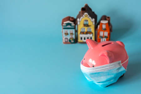 Piggy bank with medical mask in front of house models