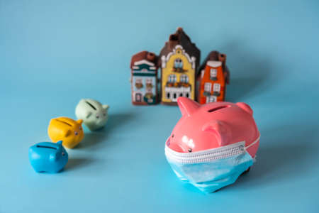Piggy bank with medical mask, small piggy banks and house models Banque d'images