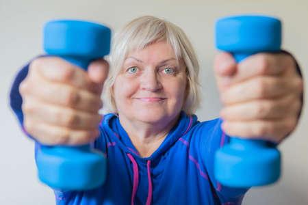 Portrait of elderly woman with dumbbells