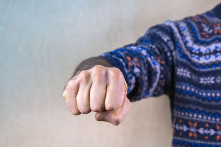 Man's fist clenched in anger. Aggressive man with a clenched fist threatens to hit. Domestic or gender violence concept. Close up, copy space