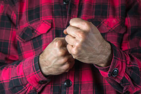 Man fists clenched in anger. Aggressive man with a clenched fist threatens to hit. Person ready to fight. Domestic or gender violence concept. Close up, copy space