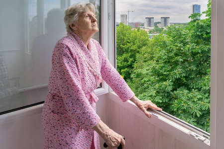 Senior woman looking at trees from her home balcony 免版税图像