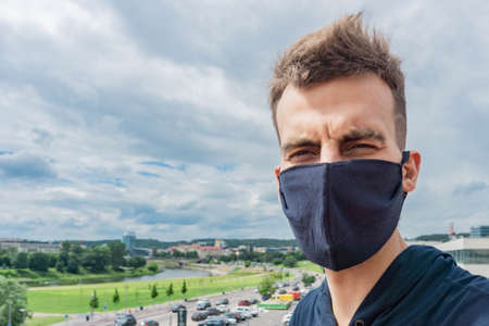 Man wearing face mask for corona virus in cityscape
