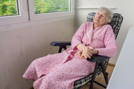 Old woman sitting on chair in terrace and looking outside