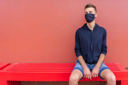 Man in protective mask sitting on bench outdoors