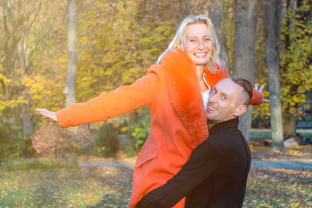 Middle-aged couple in autumn park. Smiling man holding woman in hands on colorful fall background. Happy couple on fall trees background. Couple having fun in autumn park. 免版税图像