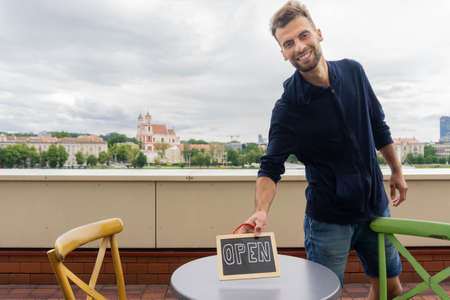 Handsome man putting chalkboard with word OPEN on table in open-air cafe. Smiling waiter holding sign OPEN in cafe outside. Bar employee with open signboard on urban background