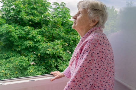 Old senior woman in balcony and taking look at trees Old lady standing in terrasse looking outside. Elderly female in balcony during quarantine. Stay at home and be safe concept. New normal.