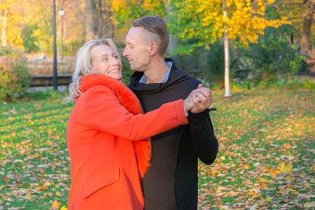 Middle-aged couple having fun in autumn park. Dancing couple on fall trees background. Man and woman hugging on colorful park. Happy family in colorful fall background.
