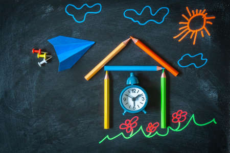 Back to school background with colored chalk drawing, school made from pencils, alarm clock, and paper plane. Top view of drawing on chalkboard for school with copy space.