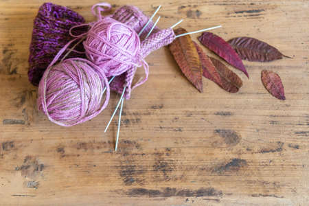 Flat lay of wool knitting and leaves with copy space on rustic wooden table. Knitted sock, ball of yarn, knitting needles, and leaves on rustic table. Cold season concept